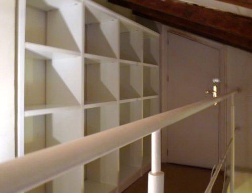 Librería para ático, construida en tablero plastificado color roble, siguiendo las alturas del techo.